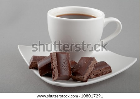 chocolate lies on a saucer with black coffee on a grey background