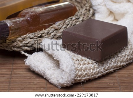 Chocolate soap on a white sponge, body oil, shampoo, gel   for body  in a basket and towel nearby.