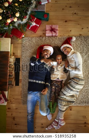 Christmas atmosphere, young family lying on floor their wooden home and making selfie