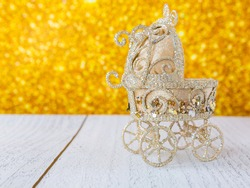 Christmas baby carriage toy on golden background