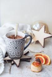 Christmas coffee in a large cup sprinkled with grated chocolate. On a light background with a knitted plaid. Decorated wooden stars, light bulbs. Cupcake with grapefruit, honey and chocolate.