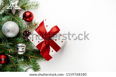 Christmas composition on a white background with white gift boxes, with a red ribbon with fir branches, toys, copy space for your congratulations