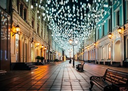 Christmas Decorations With Light Garlands Over The Night Sky in Moscow. New Year Celebration, Christmas Markets. Magical City Night. Stoleshnikov Lane night illumination