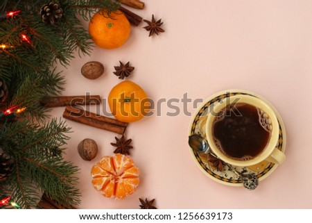 Christmas New Year composition with cup of coffee, tangerines, anise, nuts, cinnamon sticks and green fir tree branches. Holiday decoration. Copy space #1256639173
