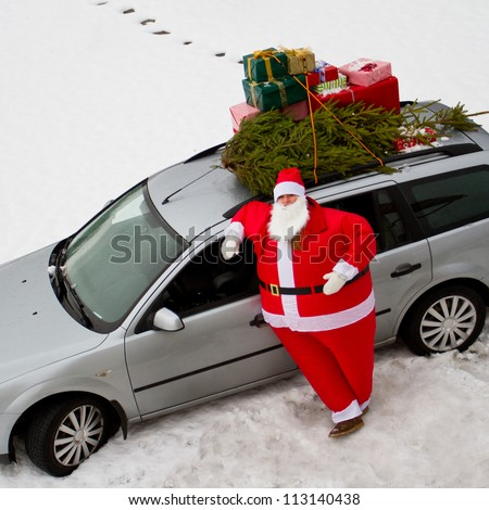 Christmas, Santa Claus - family is carrying  Christmas tree and gifts on the roof of the car