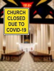 ''Church closed due to COVID-19'' information sign against a defocused church interior