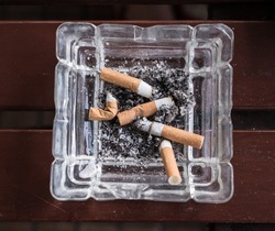 cigarette stub with ashes in the ashtray. Smoke and cancer.