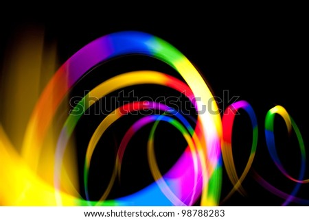 circular rainbow colored glowing light streaks isolated over a dark black background.