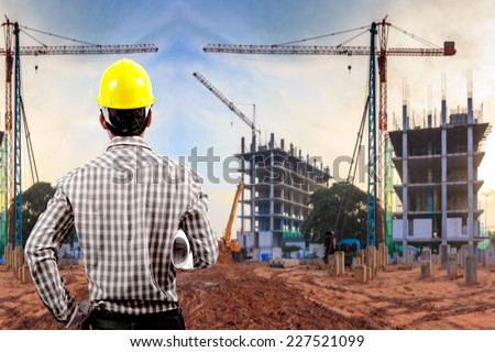 civil engineer working in building construction site against sunset sky with crane construction
