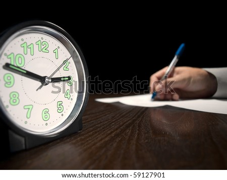 clock with a man doing written test in the background, low key, useful for job application.education and other testing related themes