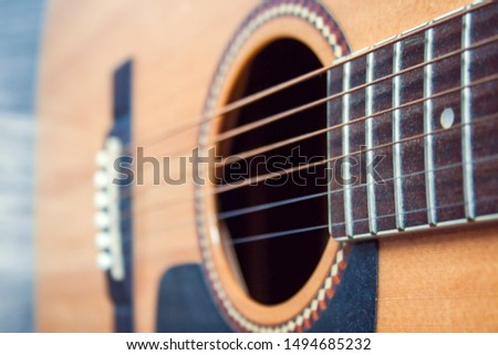 Close up acoustic zoom on the strings in a classical design guitar