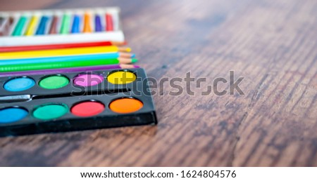 Close up and selective focus of water colours, colouring pencils and coloured chalk on a plain wooden background