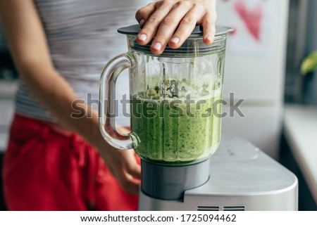 .Close-up blender process. Cooking a green spring smoothie. Mixing in a blender bowl.
