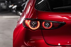 Close up detail on one of the LED red taillight modern red crossover car. Exterior detail automobile.