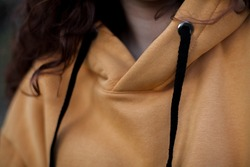close up details of oversized sand color hoodie  at female.fashion and wear concept. warm oversize wear at woman.space for text and logo.close up details of oversize wear