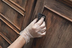 close up female hand painting an old vintage piece of furniture with a brown patina