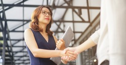 close up investor businesswoman handshake with partner vendor,collaboration of two ceo leader hand shake for agreement or deal financial cooperative concept