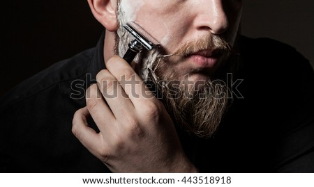 close-up of a man with a long beard and a mustache , beard shaves with a straight razor #443518918