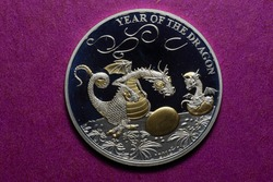 Close-up of a silver commemorative new year coin with a golden dragon and a cub with a golden egg 1000 francs CFA lying on a purple table