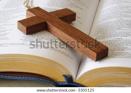 Close up of a wooden cross on a bible