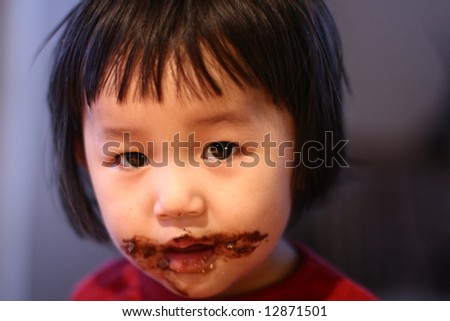close up of child head eating chocolate