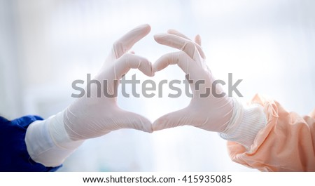 close up of doctors hands  making heart shape, cardiology concept