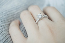 Close up of elegant diamond ring on the finger with gray Scarf background. Diamond ring.