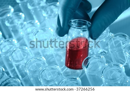 close up of gloved hand with lab test tube