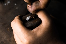 Close-up of hand of a goldsmith setting a precious stone with diamonds Ring repairing. Putting the diamond on the ring. Craft jewelery making with professional tools.