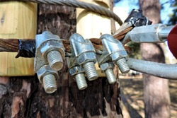 Close-up of metal ropes held together by clamps and bolts, steel wire rope and metal clamp are part of  structure of  rope park