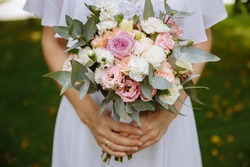 Close-up of the hands of a bride who is holding a wedding bouquet of flowers. Wedding day.