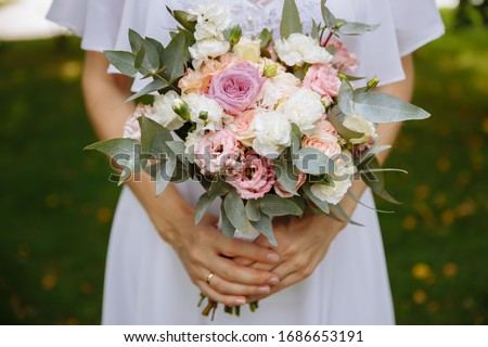 Close-up of the hands of a bride who is holding a wedding bouquet of flowers. Wedding day. Stock foto ©