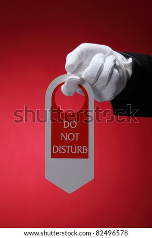 close up of the hotel staff holding a door sign do not disturb