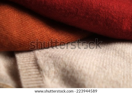 Close-up of three folded woolen sweaters. Light brown, orange and red