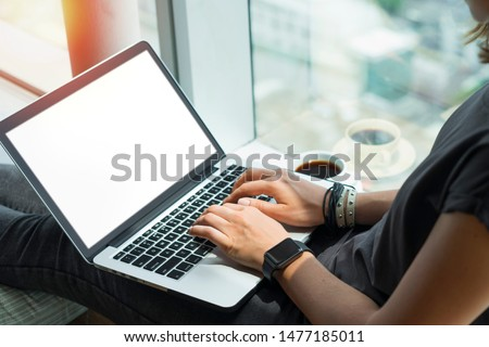 Close up of woman hands typing on keyboard. Young casually dressed female freelancer working home sitting on windowsill. Laptop with blank white screen. Mock up, copy spzce for your text.