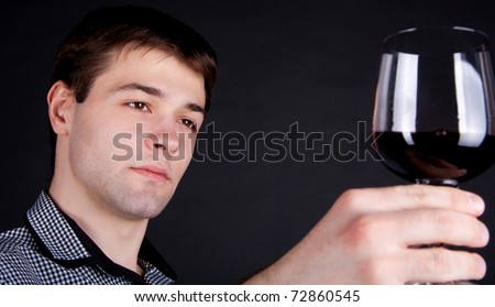 close-up of young Man evaluating the quality   of red wine