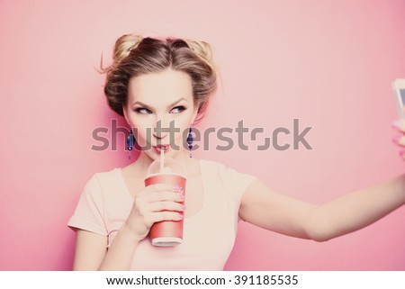 Stock Photo   close-up portrait of a beautiful young blonde girl in fashionable sunglasses on a pink background in  studio in a dress  holding a popular phone smiling It makes selfie drink through a straw drink