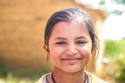Close-up portrait of adorable little Indian girl looking at camera standing in front of her village mud house. Selective focus with shallow depth of field.