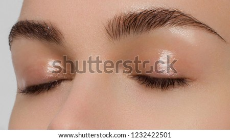 Close-up portrait of closed female eyes with natural make-up and well-groomed thick eyebrows. Trendy trendy wet makeup and long natural eyelashes. Spa treatments and beauty treatments #1232422501