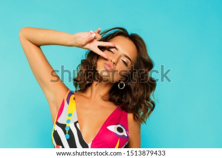 Close up portrait of  sexy brunette woman with curly short hairs  in bright plungle swimsuit  posing in studio on blue background isolate. Holiday and vacation fashion trend.  #1513879433