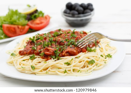 close up spaghetti bolognese on a wood table with salad