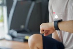 close up young man using smart watch to monitoring about healthcare tracker with virtual display to measure heart rate and calories while workout and rest for technology and futuristic life concept