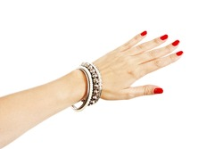 Closeup hands of young woman with red manicure polished nails wearing many silver bangles and pearl bracelets. Isolated on white background