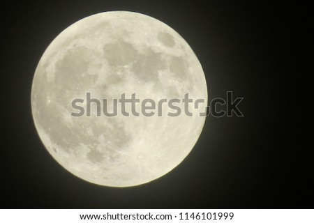 closeup of a full moon showing craters