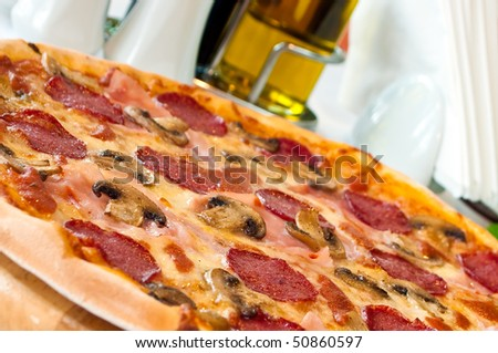 Closeup of a pizza with salami and mushrooms