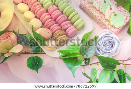 Stock Photo  Closeup photo of tasty desert sweet macarons set biscuits  on a wedding festival , ceremony . Table of fourchette . decorated with pink roses and green leafs.