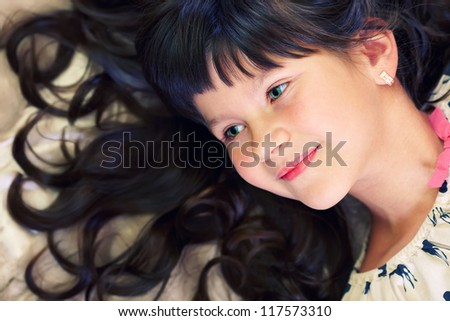 closeup portrait of beautiful little girl with curly hair and green eyes