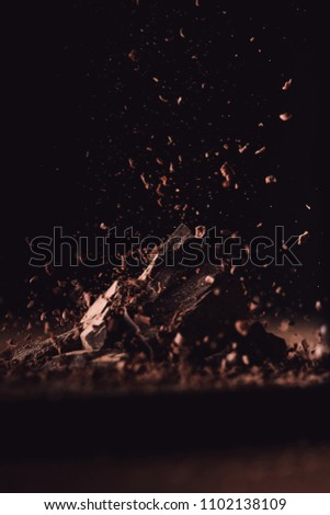 closeup view of grated dark chocolate falling on pieces of chocolate on black background