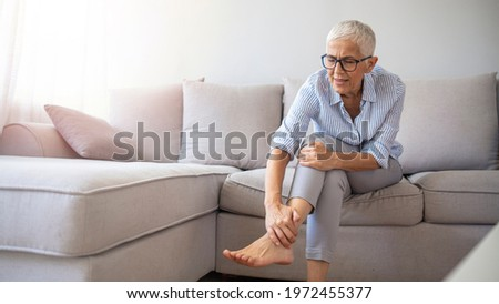 Closeup young woman feeling pain in her foot at home. Healthcare and medical concept. Tired and aching female feet after walking. Woman with feet intense pain sitting on a couch at home. ストックフォト ©