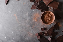 cocoa powder and chocolate bar pieces on gray abstract background.